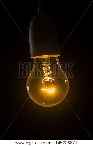 incandescent light bulb turned on in the dark key