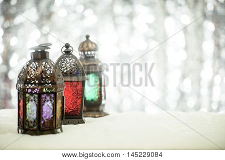 Eid and Christmas theme background with lanterns and shimmery glitter silver background