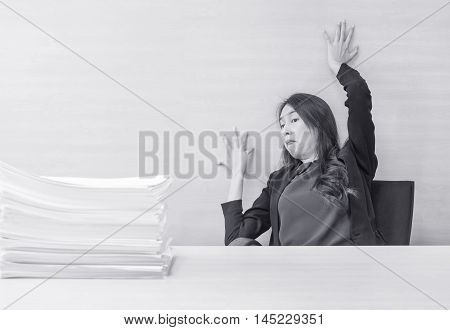 Closeup joke action of working woman are afraid pile of work paper in front of her in work concept on blurred wooden desk and wooden wall textured background in the office room in black and white tone