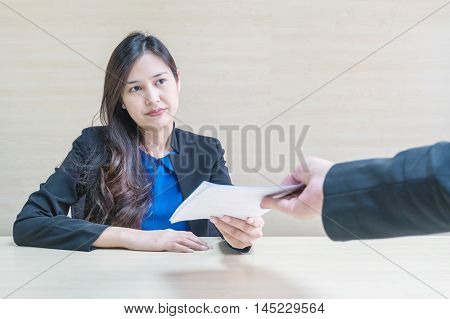 Closeup asian working woman receive work document from her boss with unwilling face in meeting room on blurred wooden desk and wall textured background in work concept