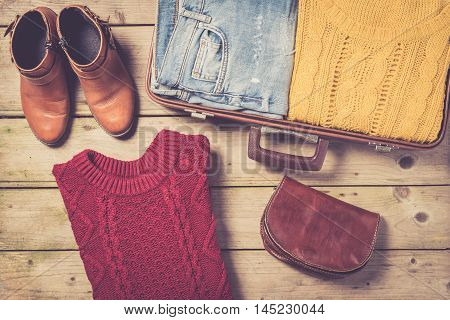 Open suitcase with casual female clothes. Close up