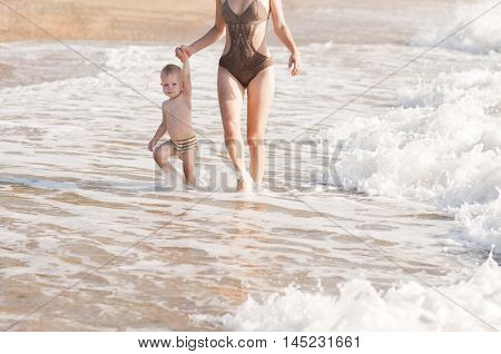 Mother and son holding hands walking along the seashore bathed in frothy waves