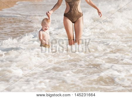 a happy child with her mother playing in the sea