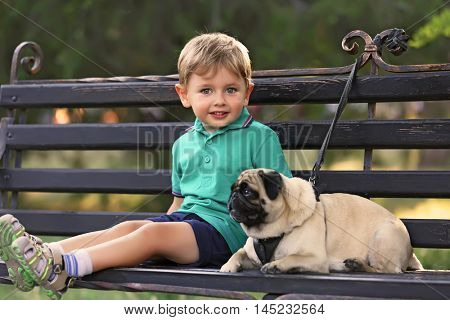 Little boy with his pug dog sitting on a bench