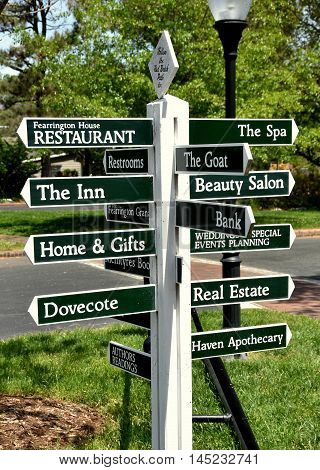 Chapel Hill North Carolina - April 19 2016: Wooden signpost directory points to the shops and restaurants at the Fearington Village residential housing development