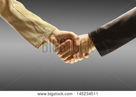 Handshake of two businessmen on a gray background.