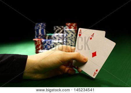 Poker chips and a hand flip the cards isolated against green felt