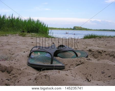 Flops left bather on the sandy shore of a small lake