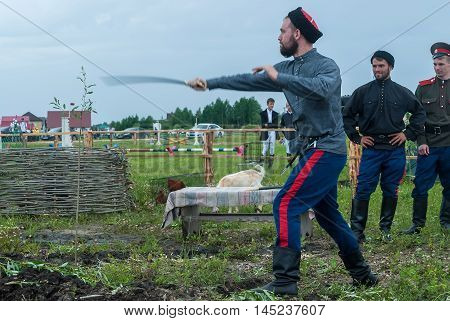 Tyumen, Russia - June 24, 2016: The 5th open championship of Russia on a plowed land. Cossack shows skill of sabre possession