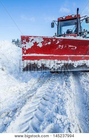 Big snow plow machine on snowy road