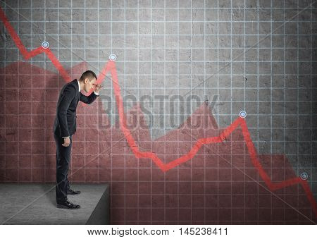Side view of a businessman shading his eyes with his hand looking at falling diagram. Economic and financial crisis. Stock market selloff.