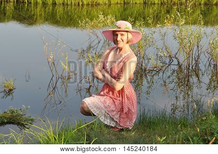 The beautiful woman in a hat smiles having sat down at a pond