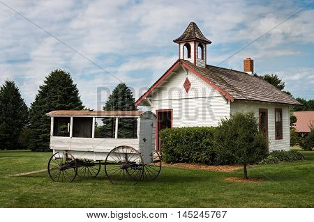 One Room Schoolhouse With School Wagon sitting in front of it