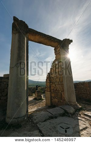 An archway of the roman ruins of Volubilis on a sunny day with blue sky. It's lochated in the area Fes- Meknes in Morocco.
