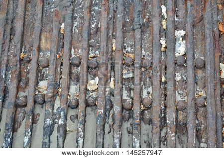 Close up of scrap iron on the beach with shells embedded