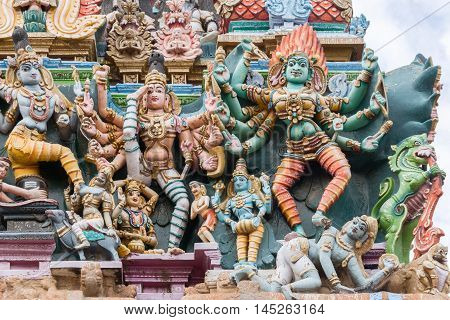 Madurai India - October 19 2013: Closeup of two images representing the fierce goddess Kali. In one she defeats the Man. Facade of South Gopuram at Meenakshi Temple.