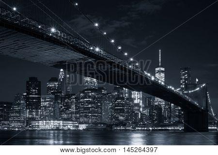 The skyline of downtown Manhattan and the Brooklyn Bridge illuminated at night
