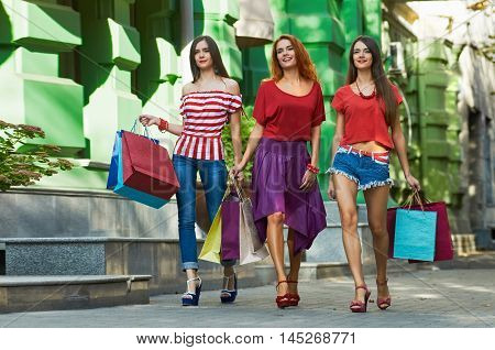 Walking around. sisters triplets Women walking with Shopping Bags On City Street