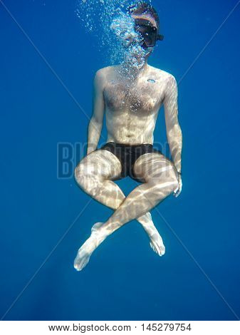 Portrait of a young causasian man meditating in the lotus position underwater. Submerged under water free diving crossed legs wearing a mask and blowing bubbles.