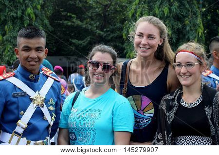 Jakarta, Indonesia - August 17, 2016: Women's spectators poses with a military Navy cadet after independence day flag ceremonial at Indonesian Presidential Palace.