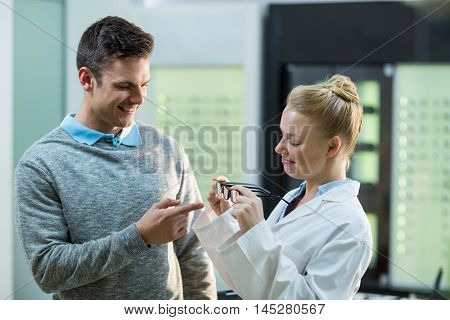 Female optometrist prescribing spectacles to patient in ophthalmology clinic