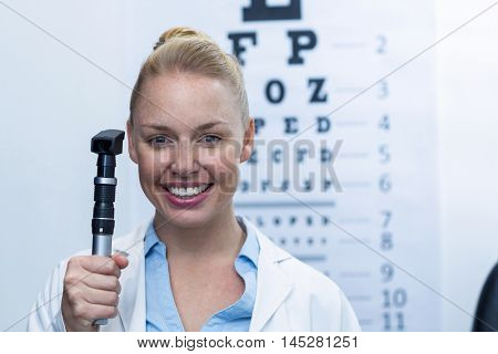 Portrait of female optometrist holding ophthalmoscope in ophthalmology clinic
