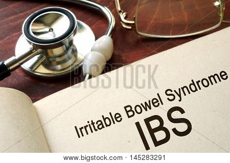 Book with words irritable bowel syndrome IBS on a table.