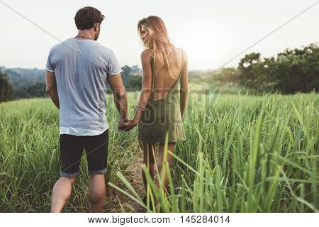 Young Couple Walking Through Grassy Road