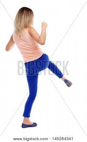 back view of standing girl pulling a rope from the top or cling to something. Isolated over white background. The blonde in a pink t-shirt has a knee.