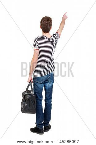 back view of pointing man with bag. backside view of person. Isolated over white background. Curly boy in a striped vest holding a bag in his hand and shows up finger.