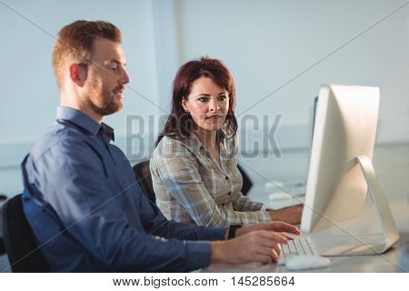 Mature students using computer in the computer room at college