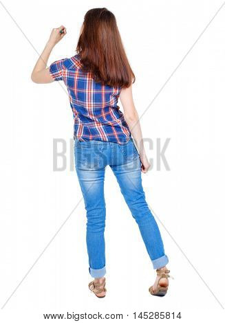 back view of writing beautiful woman. Girl in plaid shirt stands with his back and wrote marker