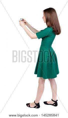 back view of standing young beautiful woman using a mobile phone. girl watching. slender brunette in a green short dress stands sideways and take pictures on the phone.