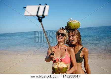 Two young women taking picture with smartphone on selfie stick on beach. Female friends in bikini enjoying summer holidays on the sea shore.