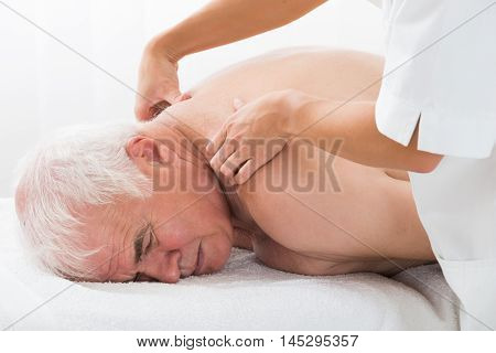Close-up Of A Senior Man Receiving Back Massage In Spa