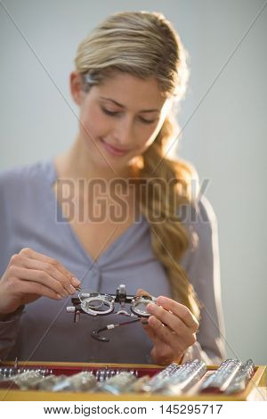 Beautiful woman preparing messbrille in optical store