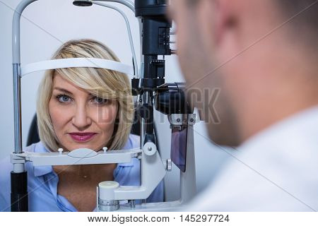 Optometrist examining female patient on slit lamp in ophthalmology clinic