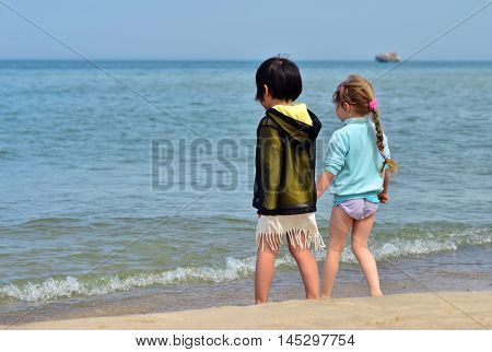 Two four years old girls on the beach. Faces not visible. Silent seascape.