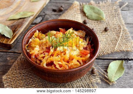 Stewed cabbage in a clay bowl and on old wooden background. Cabbage stewed with carrots, tomatoes and garlic and garnished with a sprig of dill. Vegetable recipe