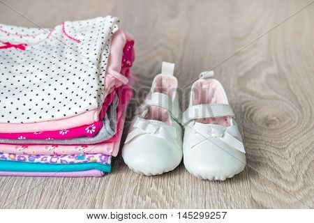 Folded Pink And White Bodysuit With Shoes On It  Grey Wooden Background. Diaper For Newborn Girl. St