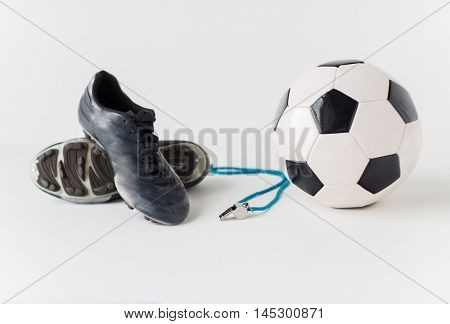 sport, soccer, football and sports equipment concept - close up of ball, referee whistle and boots