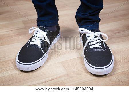 Black sports shoes. Sneakers. Modern teenage footwear.