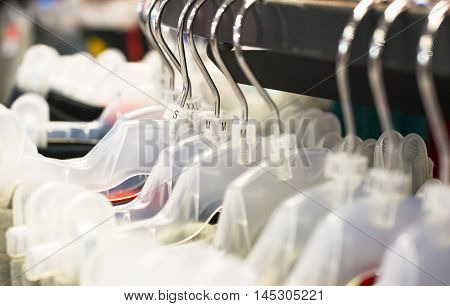 close up of plastic clothes hanger with sizing labels.