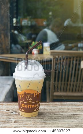 Iced Coffee In Takeaway Cup On Wood Table With Blurred Coffee Cafe Background, Light Effect On The R