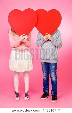 Full length portrait of happy teenage boy and girl holding red hearts over pink background. Friendship. First love. Valentine's Day.