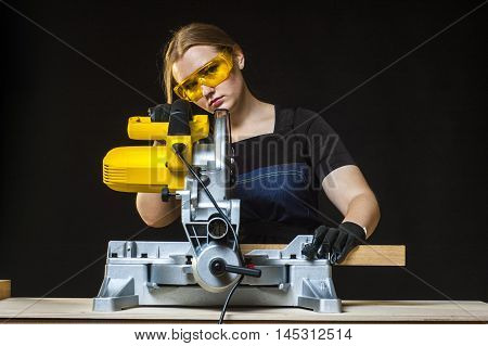young beautiful woman in overalls and glasses with disk saw preparing for cutting. Photo on black background.