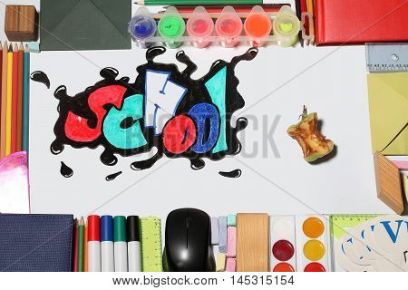 uneaten apple with worm and school text word painted graffiti with smiley eyes on paper near pencils markers computer mouse chalk ruler paint palette wooden cube notebook and alphabet on white background