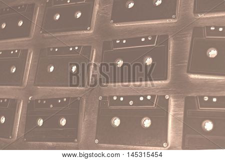 Audio cassettes are covered with white acrylic paint. Excellent retro. Creative decor. Negative Sepia effect. Secured by modern style. Vintage tapes.
