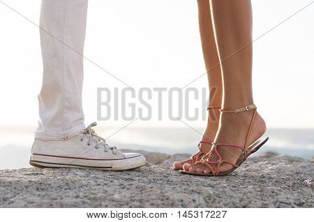Close up of legs of kissing couple on a rock at sea. Close up of feet of young man and woman on tiptoed in love during a romantic date. Young couple in love at beach.