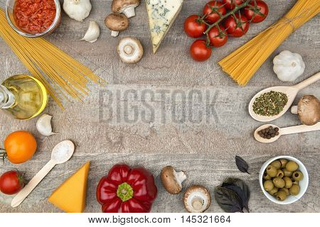 Pasta ingredients on the wooden board frame background with free space for a text